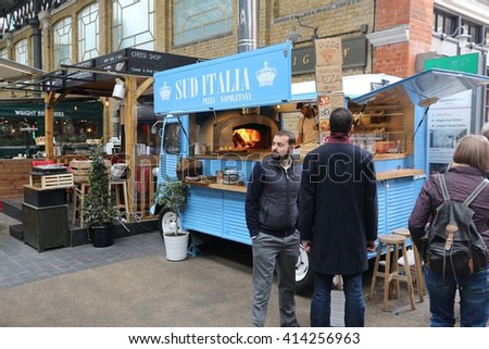 LONDON, UK - APRIL 22, 2016: People visit a food truck in Old Spitalfields Market in London. A market existed here for at least 350 years. - stock photo