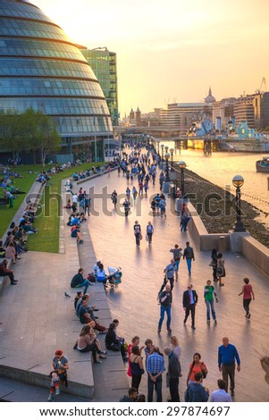 LONDON, UK - APRIL15, 2015: South bank of river Thames in sun set light. View includes a lot of walking people and London hall building - stock photo