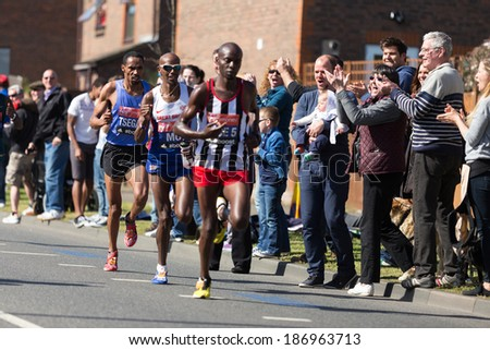 LONDON, UK - APRIL 13, 2014 - Spectators cheering Samuel Tsegay and Mo Farah as they run with the main group of marathoners at km. 15 in the Virgin Maraton April 13 in London - stock photo