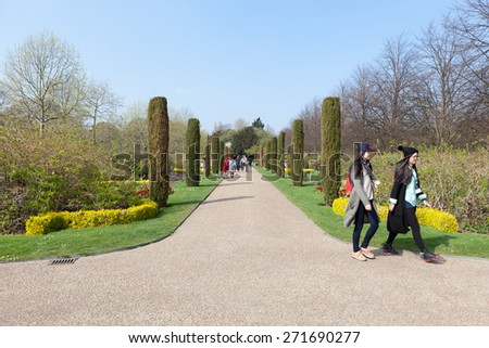 LONDON, UK - APRIL 9, 2015: Visitors to London's Royal Regent's Park enjoy walking down The Avenue Gardens on an unusually warm spring day. - stock photo