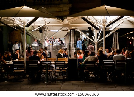 LONDON, UK - AUG 16: People enjoy dinner in a restaurant in Covent Garden in London on August 16, 2013. The Covent Garden area has over 60 restaurants and bars and is a popular night destination - stock photo