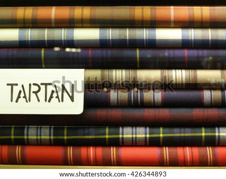 LONDON, UK - CIRCA NOVEMBER 2009: tartan fabric piled in a store for sale - stock photo