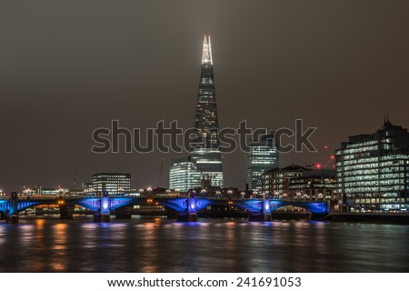 LONDON, UK - DEC 1: London skyline at night including The Shard skyscraper, Southwark Bridge and illuminated buildings under thick clouds in London on December 1, 2014 - stock photo