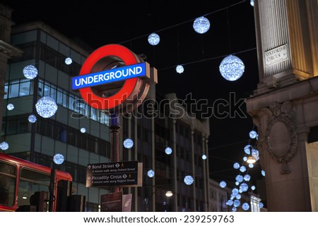 LONDON, UK - DECEMBER 20: Nighttime shot of London underground entrance sign with Christmas lights in the background. December 20, 2014 in London. - stock photo