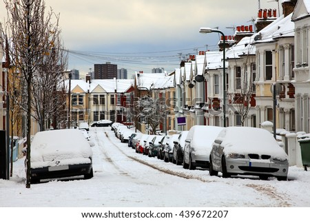 London, UK, December 18 2010 - Snow cityscape of a terraced street with slippery blizzard conditions showing cars covered with ice and snow - stock photo