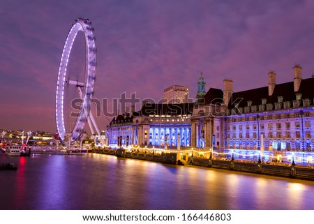 LONDON, UK - DECEMBER 8, 2013: The London Eye in the early evening showing a colourful sky and reflections in the Thames on 8th December 2013 - stock photo