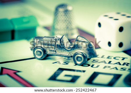 LONDON,UK - FEBRUARY 11, 2015 : Tokens and dice next to the GO space in a Monopoly game board - stock photo