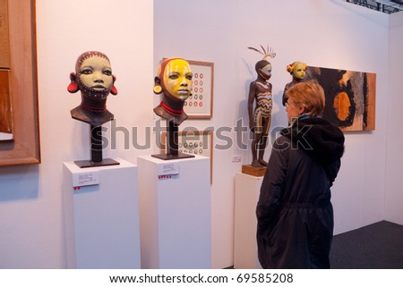 LONDON, UK-JANUARY 23: A visitor to the prestigious London Art Fair showing contemporary and modern art, looking at sculpture by artist Cathy Lewis. January 23, 2011 in London, UK. - stock photo