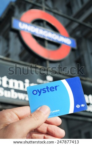 LONDON, UK - JANUARY 19: A young man holds an Oyster card at the entrance of the Underground on January 19, 2015 in London, United Kingdom. This card is used on public transport in Greater London - stock photo