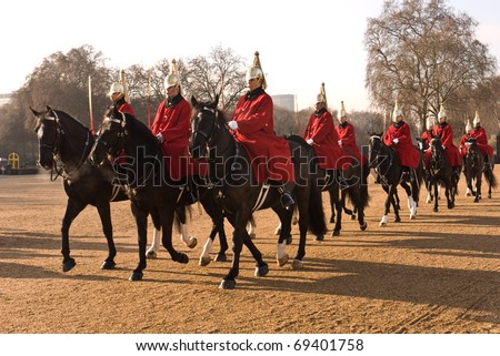 LONDON, UK- JANUARY 19: Members of the Queen's Royal Horse Guards, the Royal Life Guards Regiment, riding to the Changing of the Guard Ceremony at Horse Guards Parade. January 19, 2011 in London, UK. - stock photo