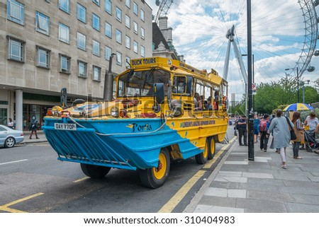 LONDON, UK - JULY 31, 2015: A London Duck Tours sightseeing bus, a very popular way of seeing the city, in-front of the London Eye in summer 2015. - stock photo