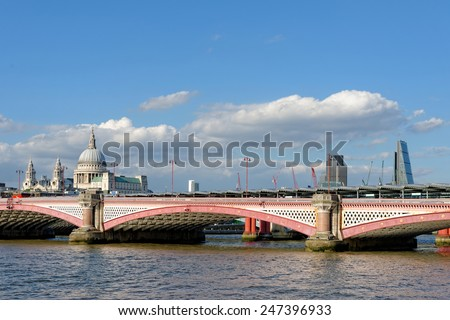 LONDON, UK - JULY 1, 2014: A view of Blackfriars bridge -  a road and foot traffic bridge, over the river Thames against a background of St Paul Cathedral, the City and the Blackfriars railway bridge. - stock photo