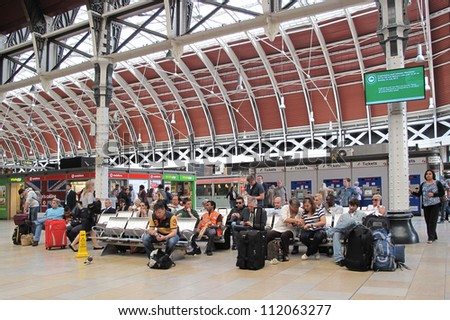 LONDON, UK - JULY 19: Passengers waiting at Paddington train station on July 19, 2012, London, UK. Station has recently been modernized,it's terminal for the dedicated Heathrow Express airport service - stock photo