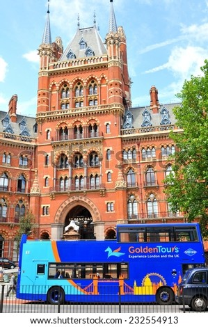 LONDON, UK - JULY 9, 2014: Tourists admire the architecture of the St. Pancras Renaissance hotel in London from a tour bus  - stock photo