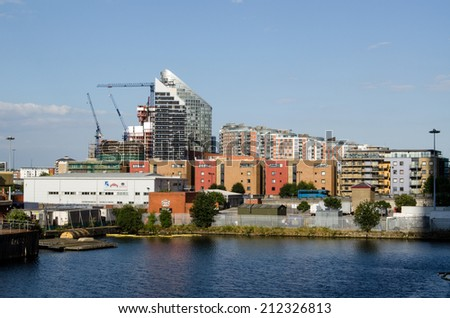 LONDON, UK  JULY 1, 2014: View across North Dock towards housing in Poplar, Tower Hamlets on the edge of London Docklands. - stock photo