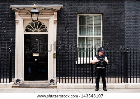 LONDON, UK - JUN 16: A  police officer guards the door of 10 Downing Street in London on June 16, 2013 as British PM David Cameron meets Russian President Vladimir Putin to discuss Syria ahead of G8. - stock photo