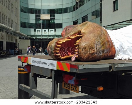 LONDON, UK - JUNE 1, 2015:  A life size model of a dead tyrannosaurus promoting the National Geographic Channel's T Rex Autopsy programme outside the BBC headquarters in Westminster, London. - stock photo