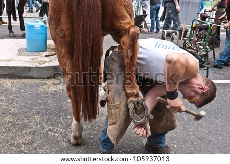 LONDON, UK-JUNE 23: A member of the ancient Worshipful Company of Farriers removes a horse shoe as part of the demonstration of their work, in the street at Cheapside. June 23, 2012 in London UK. - stock photo