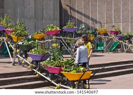 LONDON,UK-JUNE 6: An urban wheelbarrow garden is enjoyed by visitors to the Southbank's festival of neighbourhood, that brings urban gardens and allotments to the centre. June 6, 2013 London UK. - stock photo