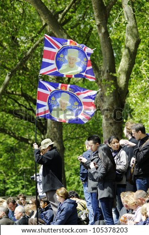 LONDON, UK - JUNE 16: Man holding two Diamond Jubilee flags during Trooping the Colour ceremony on the Mall and at Buckingham Palace, on June 16, 2012 in London. - stock photo