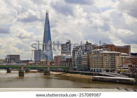 LONDON, UK - JUNE 30, 2014: Shard of glass on the river Thames, office and residential building in the City of London one of the leading centres of global finance. - stock photo