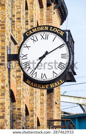 LONDON, UK, JUNE 12TH 2015 - A traditional wall clock is exposed as ensign on the brick wall outside the famous shop and food market of Camden Town, London - stock photo