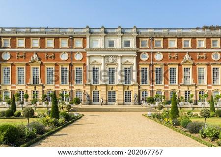 LONDON, UK - JUNE 4, 2013: View of Hampton Court Palace in London. Hampton Court was originally built for Cardinal Thomas Wolsey, a favorite of King Henry VIII, circa 1514. - stock photo
