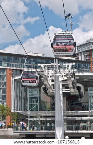 LONDON, UK-JUNE 30:Visitors travel on Emirates Air Line cable cars. The service is the UK's first urban cable car running across the Thames from the O2 to the Excel centre  June 30, 2012 in London UK - stock photo