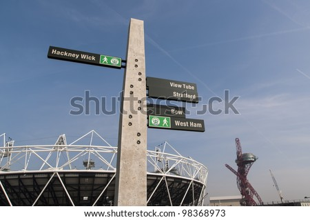LONDON, UK - MARCH 24: Details shot of sign post with Olympic stadium in the background on March 24, 2012 in London. All locations around the Olympic Park are undergoing redevelopment works. - stock photo