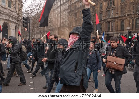 LONDON, UK- MARCH 26: Masked Anarchists march on their way to occupy and protest in central London, during a day of action against government cuts. March 26, 2011 in London, UK. - stock photo