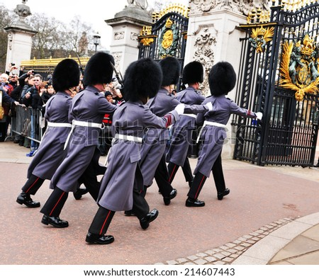 LONDON, UK - MARCH 8, 2011: Tourists watch the changing of the Guard at Buckingham Palace - stock photo