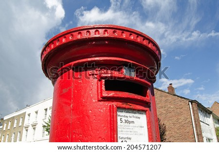 LONDON, UK - MAY 24, 2014:  A bright red pillar box on a street corner, part of the Royal Mail infrastructure that operates across the UK. - stock photo