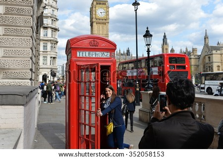 LONDON, UK - MAY 30, 2015: A tourist poses for a photo by a traditional red phonebox in Westminster. The British capital is one of the world's most visited cities with 17 million visitors in 2013. - stock photo