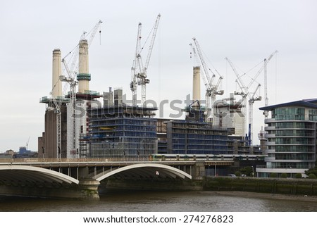 LONDON, UK - MAY 01: Battersea power station surrounded by cranes and scaffoldings. May 01, 2015 in London. The chimneys of the emblematic structure are being rebuilt as part of its redevelopment. - stock photo