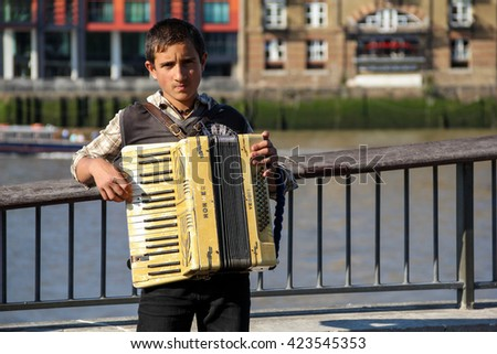 London, UK - May 10, 2015 - Immigrant busker playing accordion on London's South Bank - stock photo