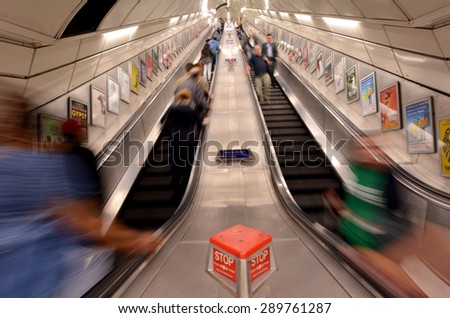 LONDON, UK - MAY 12 2015:Passengers on London Underground escalator. The Deepest station below street level is Hampstead (Northern line) - 58.5 metres. - stock photo