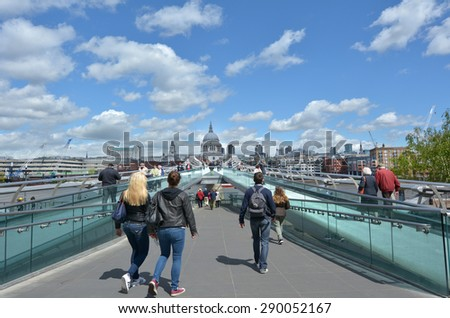 LONDON, UK - MAY 12 2015:Pedestrian cross over the Millennium Bridge in London, UK.Millennium Bridge suspension cables support a working load of 5,000Ã?Â??people on the bridge at one time. - stock photo