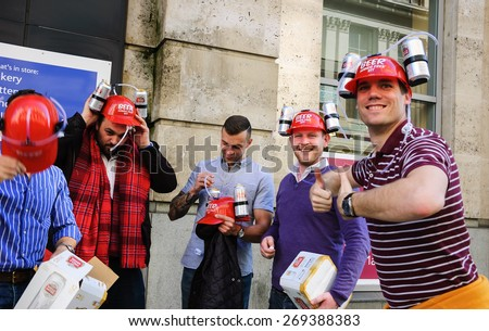 "LONDON, UK - MAY 3, 2014: Unidentified men wear ""Beer Hands Free Kit"" (specially designed hat for drinking beer) with Stella Artois cans. This gadget becoming popular among partying young people. - stock photo"