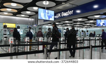 LONDON, UK - NOV 18, 2015: Air travelers queue at border passport control entrance gates at Heathrow Airport. The British aviation hub is the busiest in the European Union by passenger traffic. - stock photo