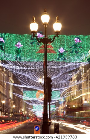 London, UK - November 12, 2011: Christmas lights display along Regent Street ,with blurred light trails from passing vehicles, during the festive season - stock photo