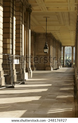 LONDON, UK - NOVEMBER 29: Column throw shadows in a corridor of the Royal Naval College in Greenwich where tourists standing at this end on November 29, 2014 in London / Royal Naval College - stock photo