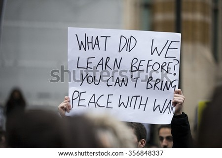 LONDON, UK - NOVEMBER 28, 2015 Unidentified protester holding a protest banner during demonstration again UK bombing Syria outside Downing Street in Whitehall.  - stock photo
