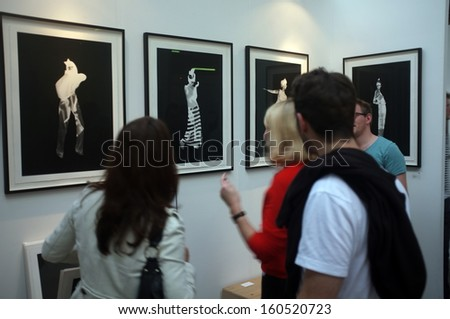 LONDON, UK - OCTOBER 20,2013: Art enthusiasts view the artwork during Moniker Art Fair (and its partner The Other Art Fair) at The Old Truman Brewery in Brick Lane. - stock photo