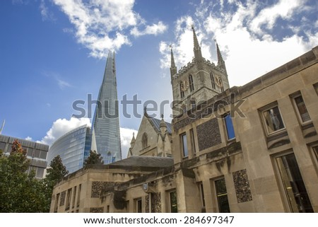 LONDON, UK - OCTOBER 16, 2014: Southwark Cathedral and Shard building. South bank walk of the river Thames. Contrast of modern and old arhitecture. - stock photo