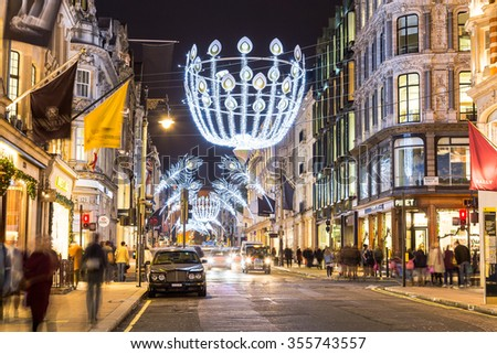 LONDON, UK - 23RD DECEMBER 2015: A view down New Bond Street in London during the Christmas period showing building exteriors, decorations, people and traffic. - stock photo