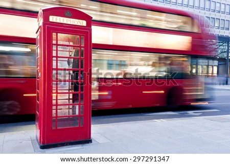London, UK. Red telephone booth and red bus passing in motion blur. Symbols of Great Britain, United Kingdom, England. - stock photo