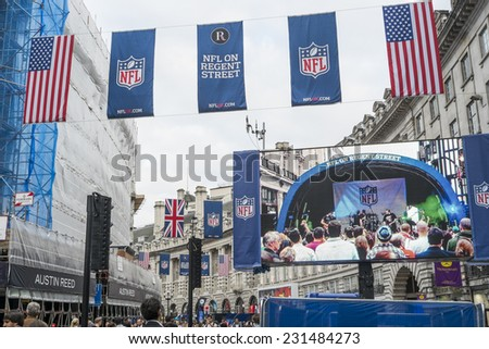 LONDON, UK - SEPTEMBER 27: American flag and NFL banners hanging above screen on Regent street. September 27, 2014 in London. Regent street was closed to traffic to host NFL related games and events. - stock photo