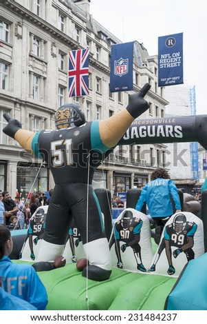 LONDON UK - SEPTEMBER 27: Jacksonville Jaguars inflatable player and NFL flags in Regent Street. September 27 2014 in London. The street was closed to traffic to host NFL related games and events. - stock photo