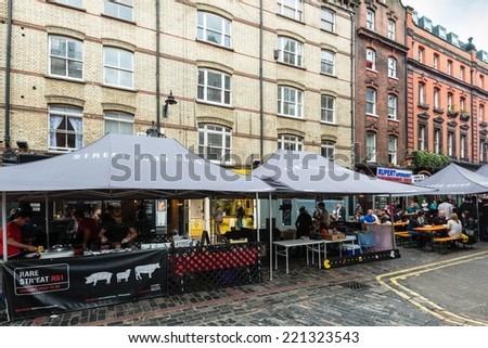 LONDON, UK - SEPTEMBER 26, 2014: People are buying freshly prepared finger food on the London Street Food Union market in Soho on September 26, 2014 in London, UK. Street food has its roots in the - stock photo