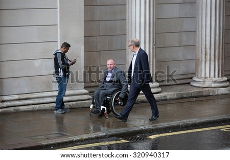 LONDON, UK - SEPTEMBER 17, 2015: Two businessmen  walking on the street against of Bank of England wall  - stock photo